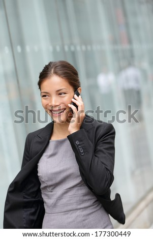 Business woman talking on smart phone smiling happy walking outdoor. Young multiracial Asian female professional smiling having conversation on mobile smartphone New York City, Manhattan, USA. - stock photo