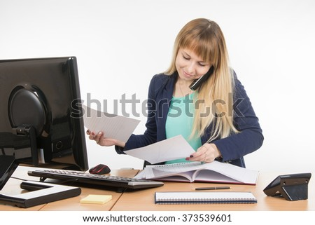 Business woman talking on the phone and looking at the paper documents