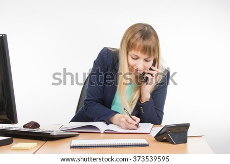 Business woman talking on the phone in the office writes book - stock photo