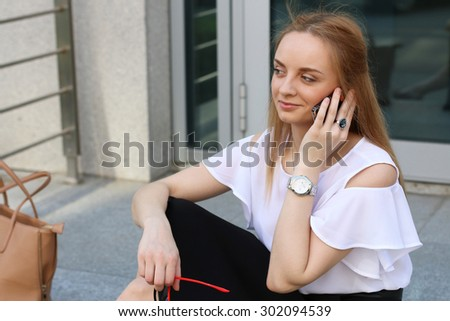 Business woman talking on the phone near moder office
