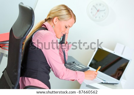 Business woman talking phone and writing in notepad - stock photo
