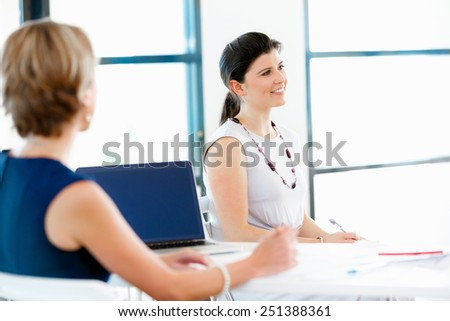 Business woman talking to her collegues in office - stock photo
