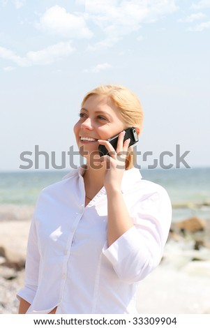 business woman talks by phone on a beach - stock photo