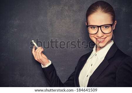 business woman teacher with glasses and a suit with chalk   the lost in thought at a school board - stock photo