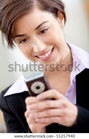 Business woman texting from her cell and smiling - stock photo
