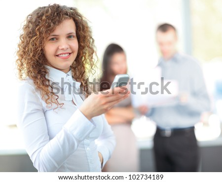 Business woman texting on her cell phone and smiling - stock photo