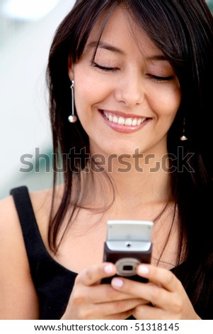 Business woman texting on her mobile phone and smiling - stock photo