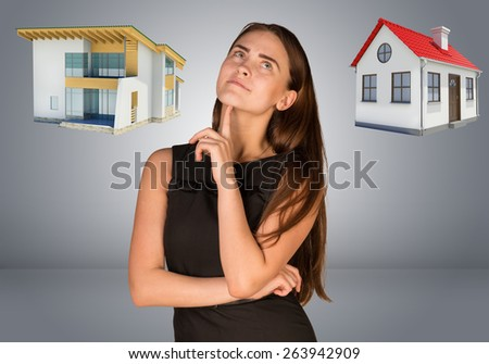 Business woman thinking over house and cottage. Gray gradient background - stock photo