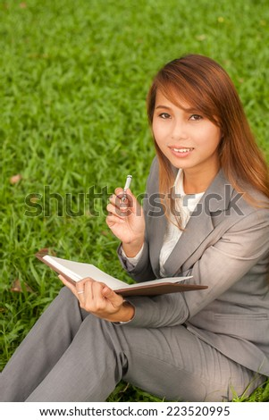 Business woman thinking solution on lunch break in city park. Young professional businesswoman sitting and thinking on green grass in city park.  - stock photo