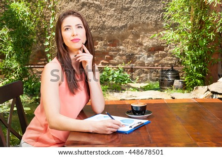 Business woman thinking with clipboard outside on terrace with coffee aside and copy advertising area