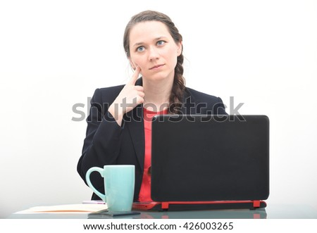 Business woman thinking with finger on cheek while at desk - stock photo