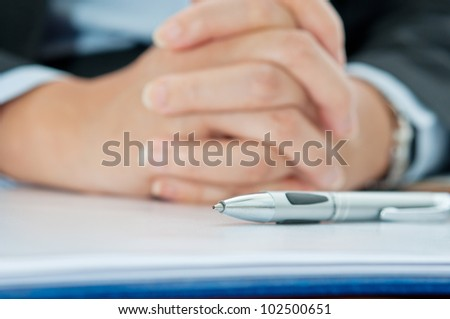 Business woman thinking with pen - stock photo
