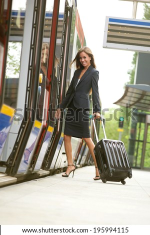 Business woman traveling with suitcase by train - stock photo