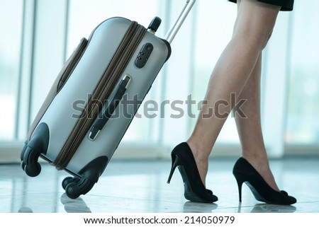 Business woman traveling with trolley. Women's legs, close-up - stock photo