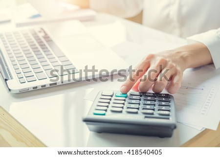 business woman using a calculator to calculate the numbers in a office - stock photo
