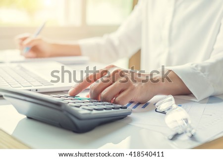 business woman using a calculator to calculate the numbers in a office