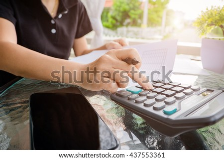Business woman using a calculator to calculate the numbers on his desk in outdoor - stock photo