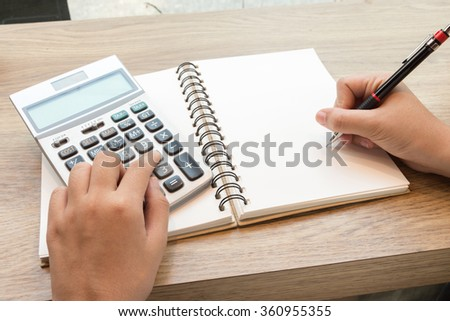 Business woman using calculator for calculating data concept - stock photo