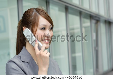 Business woman using cellphone with happy smiling expression, half length closeup portrait in outside of modern buildings. - stock photo