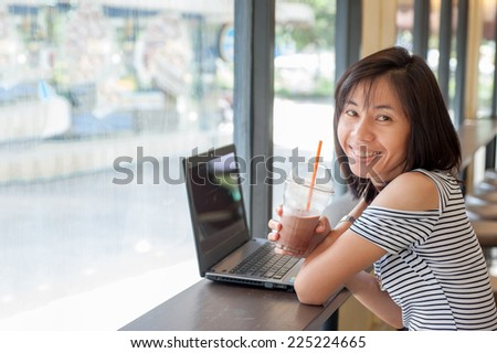 Business woman using computer sitting in a cafe with cocoa spin put on the right hand side.