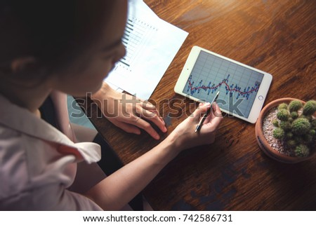 Business woman using laptop for work and trade stock or look graph in office
