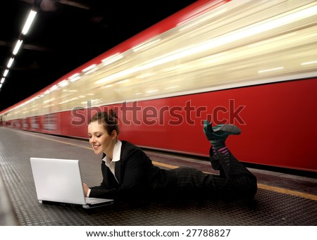business woman using laptop in a subway station - stock photo