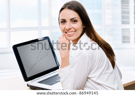 Business woman using laptop in office - stock photo
