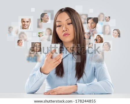 Business woman using smartphone. Many people portraits around her - stock photo