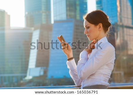 Business woman using smartphone. Urban background