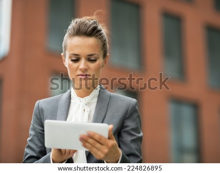 Business woman using tablet pc in front of office building - stock photo