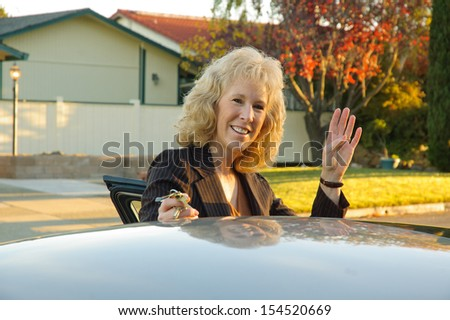 Business woman waving as she gets into her car - stock photo
