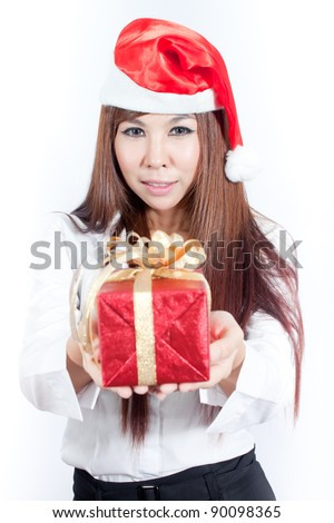 Business woman wearing a santa hat and holding a christmas gift - stock photo
