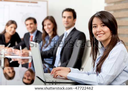 Business woman with a laptop at the office with a group behind - stock photo