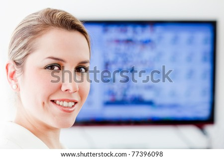 Business woman with a screen behind her - stock photo