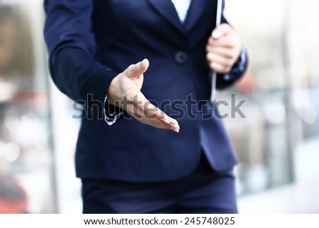 Business woman with arm extended for a handshake - stock photo