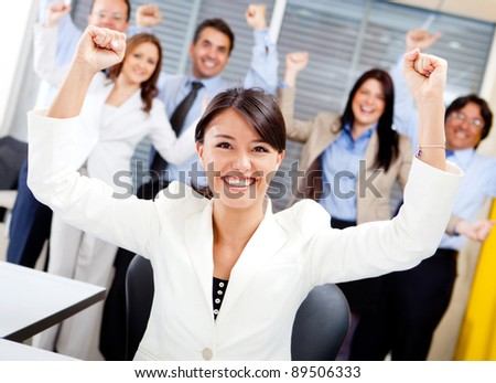 Business woman with arms up leading a successful team - stock photo