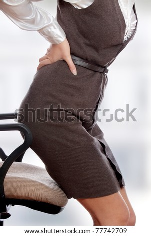 Business woman with back pain after long work on chair. - stock photo