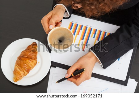 Business woman with bar chart, coffee and snack
