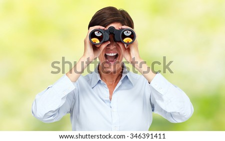 Business woman with binoculars over green background. - stock photo