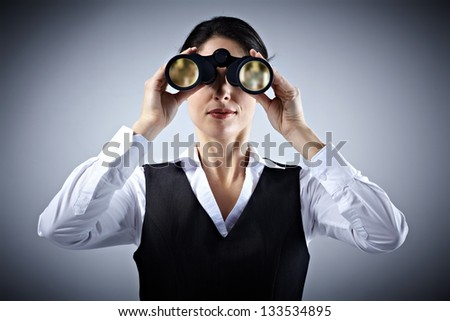 Business woman with binoculars spying on competitors. - stock photo