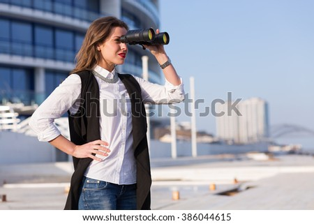 Business woman with binoculars standing outside a business building