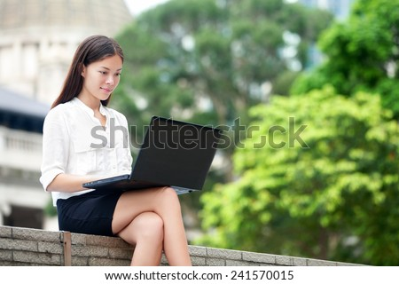 Business woman with computer laptop working outside looking at screen in business district, Central, Hong Kong. Young female professional businesswoman sitting outdoors. Asian Chinese Caucasian woman. - stock photo