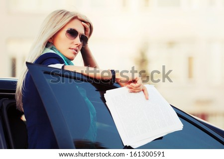 Business woman with financial papers at the car - stock photo