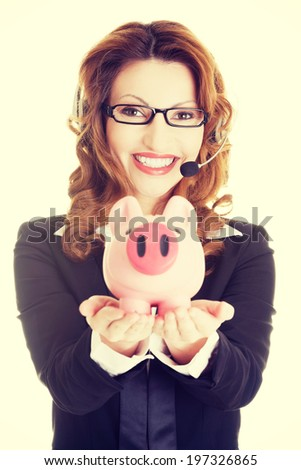 Business woman with headset holding piggy bank. - stock photo