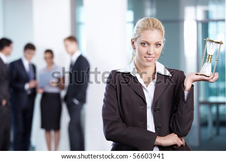 Business woman with hourglass in the foreground - stock photo