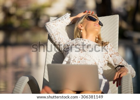 Business woman with laptop computer relaxing on vacation - stock photo