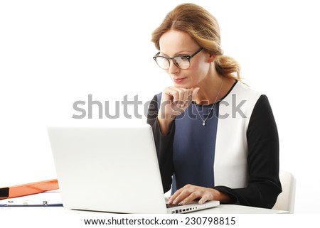 Business woman with laptop sitting at desk and typing. Isolated on white background.  - stock photo