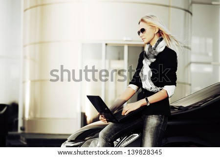 Business woman with laptop sitting on the car - stock photo