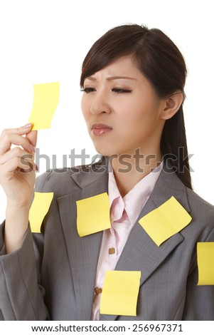 Business woman with many yellow memo note on her body, closeup portrait. - stock photo