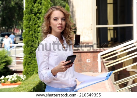 Business woman with mobile phone on city street